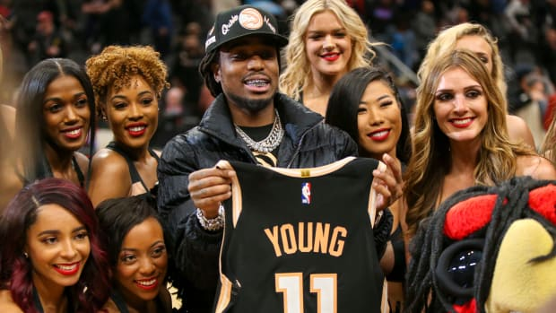 Rapper Quavo celebrates with cheerleaders while holding the jersey of Atlanta Hawks guard Trae Young (not pictured) after a victory against the Miami Heat at State Farm Arena.