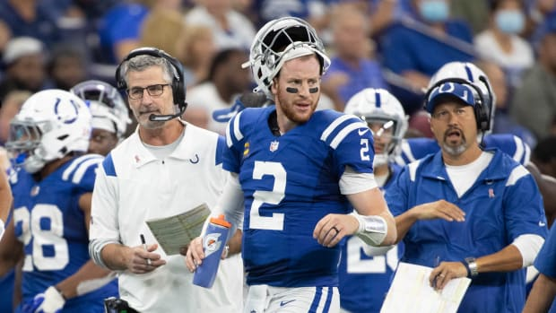 Sep 12, 2021; Indianapolis, Indiana, USA; Indianapolis Colts head coach Frank Reich and Indianapolis Colts quarterback Carson Wentz (2) talk during a timeout in the second quarter against the Seattle Seahawks at Lucas Oil Stadium.