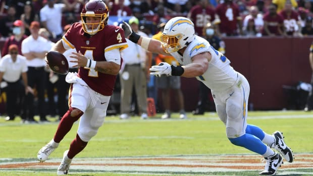 Sep 12, 2021; Landover, Maryland, USA; Washington Football Team quarterback Taylor Heinicke (4) i tackled by Los Angeles Chargers defensive end Joey Bosa (97) during the second half at FedExField.