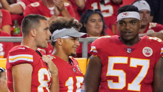 Aug 27, 2021; Kansas City, Missouri, USA; Kansas City Chiefs tight end Travis Kelce (87) and quarterback Patrick Mahomes (15) and offensive tackle Orlando Brown (57) watch play on the sidelines against the Minnesota Vikings during the game at GEHA Field at Arrowhead Stadium. Mandatory Credit: Denny Medley-USA TODAY Sports