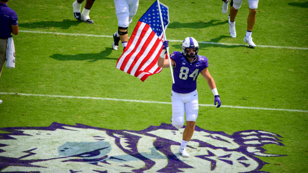 Sep 11, 2021; Fort Worth, Texas, USA; TCU Horned Frogs tight end Dominic DiNunzio (84) carries an American flag as he leads his team on to the field before the game between the TCU Horned Frogs and the California Golden Bears at Amon G. Carter Stadium.