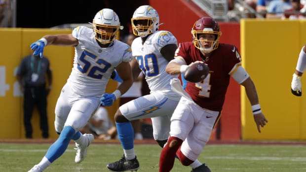 Sep 12, 2021; Landover, Maryland, USA; Washington Football Team quarterback Taylor Heinicke (4) scrambles with the ball past Los Angeles Chargers linebacker Kyler Fackrell (52) in the fourth quarter at FedExField. Mandatory Credit: Geoff Burke-USA TODAY Sports