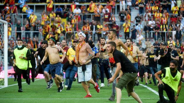 Lens fans storm the field against Lille.