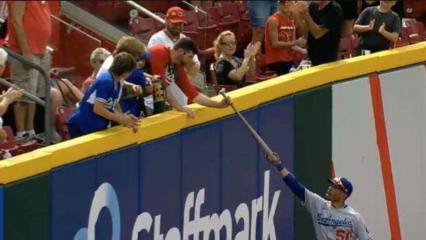 Mookie Betts gives his bat to a Reds fan.