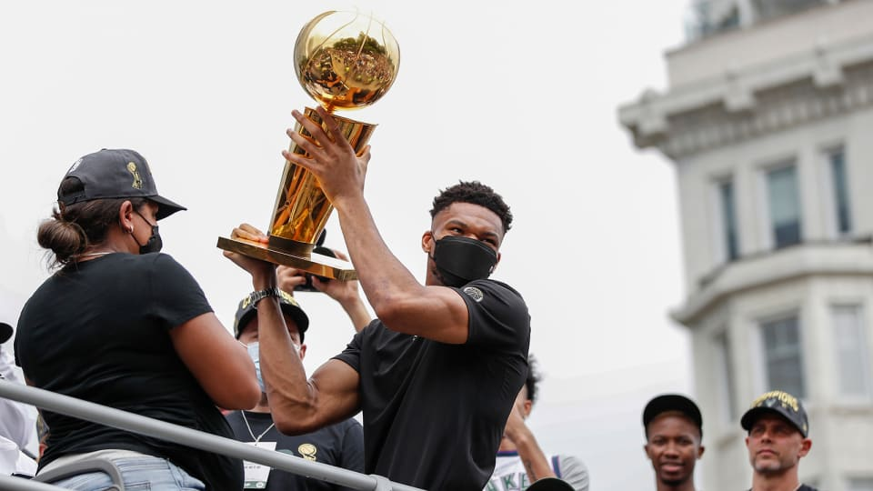 Bucks' Giannis Antetokounmpo hoisting the Larry O'Brien trophy during the championship parade in Milwaukee