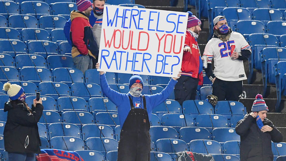 """A Buffalo Bills fan holds up a """"Where Else Would You Rather Be?"""" sign at a game during the COVID pandemic"""