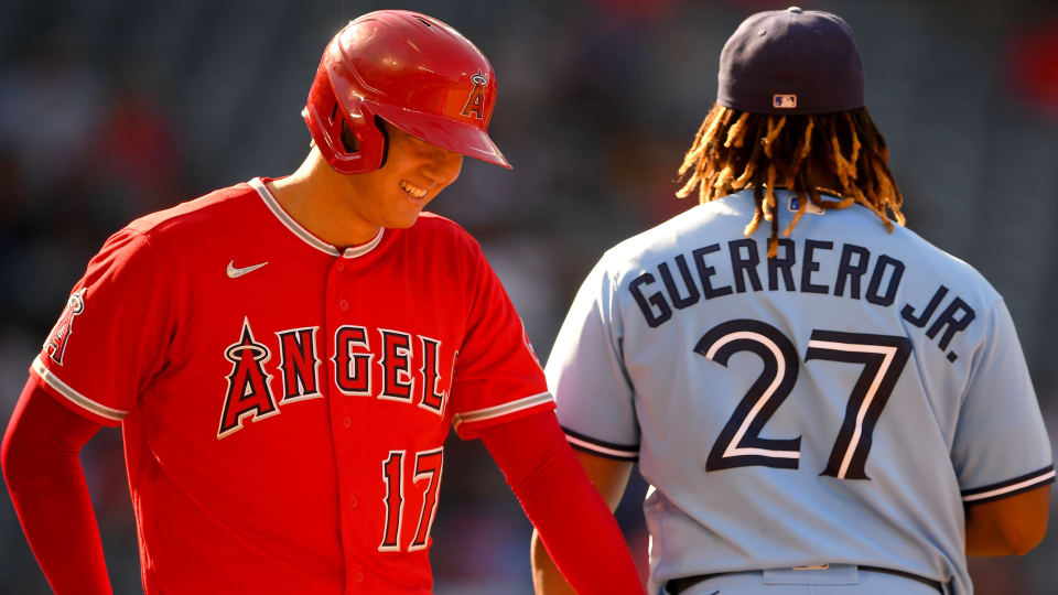 Los Angeles Angels designated hitter Shohei Ohtani (17) smiles at Toronto Blue Jays first baseman Vladimir Guerrero Jr. (27) after drawing an intentional walk in the sixth inning at Angel Stadium.