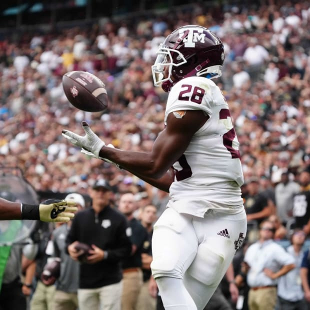 Sep 11, 2021; Denver, Colorado, USA; Texas A&M Aggies running back Isaiah Spiller (28) pulls in a touchdown pass Colorado Buffaloes linebacker Guy Thomas (1) in the fourth quarter at Empower Field at Mile High. Mandatory Credit: Ron Chenoy-USA TODAY Sports