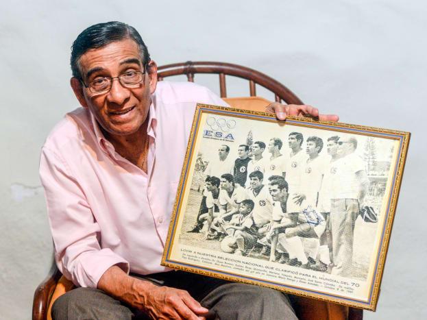 Salvador Mariona displays a photo of the 1970 El Salvador World Cup team.