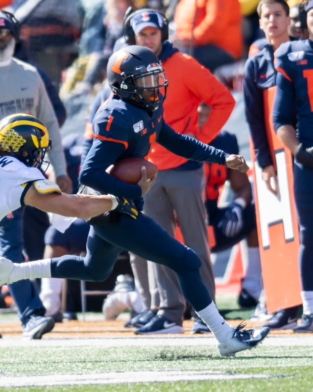 Michigan linebacker Jordan Glasgow (29) tackles Illinois quarterback Isaiah Williams (1) during the first half of Michigan's 42-25 win at Memorial Stadium.