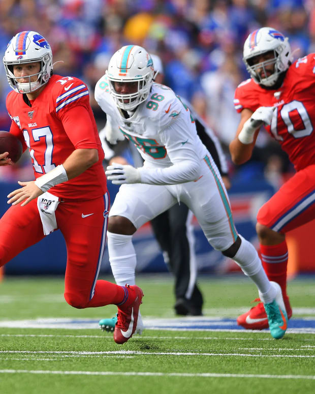 Oct 20, 2019; Orchard Park, NY, USA; Buffalo Bills quarterback Josh Allen (17) runs with the ball in front of Miami Dolphins defensive end Taco Charlton (96) during the first quarter at New Era Field. Mandatory Credit: