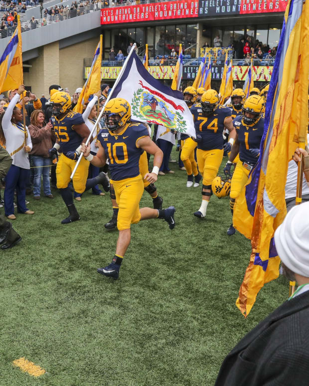 West Virginia Mountaineers linebacker Dylan Tonkery (10) leads the West Virginia Mountaineers onto the field prior to their game against the Oklahoma State Cowboys at Mountaineer Field at Milan Puskar Stadium