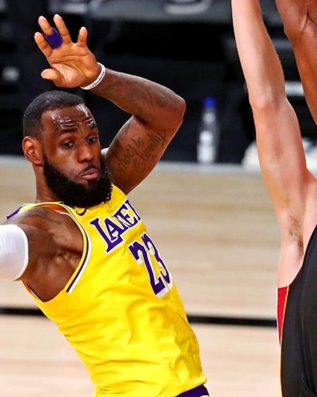 Los Angeles Lakers forward LeBron James (23) passes the ball against Miami Heat forward Bam Adebayo (13) during the third quarter in game one of the 2020 NBA Finals at AdventHealth Arena.