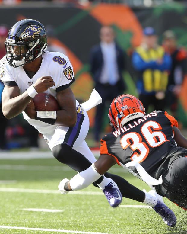 Nov 10, 2019; Cincinnati, OH, USA; Baltimore Ravens quarterback Lamar Jackson (8) breaks a tackle by Cincinnati Bengals strong safety Shawn Williams (36) during the first quarter at Paul Brown Stadium. Mandatory Credit: Joe Maiorana-USA TODAY Sports
