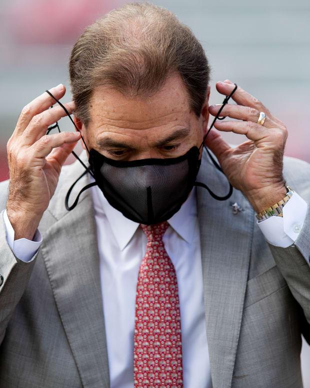 Nick Saban putting on a mask