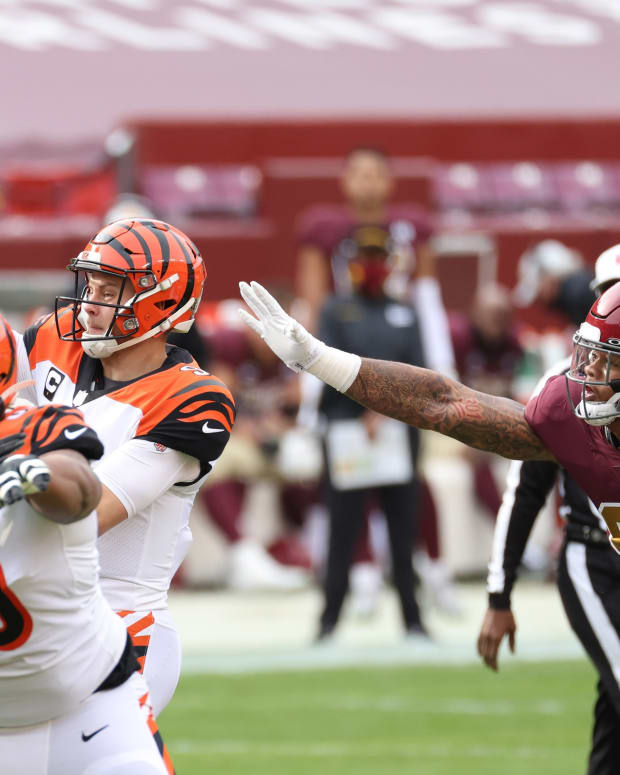 Nov 22, 2020; Landover, Maryland, USA; Cincinnati Bengals quarterback Joe Burrow (9) passes the ball under pressure from Washington Football Team defensive end Chase Young (99) in the first quarter at FedExField. Mandatory Credit: Geoff Burke-USA TODAY Sports