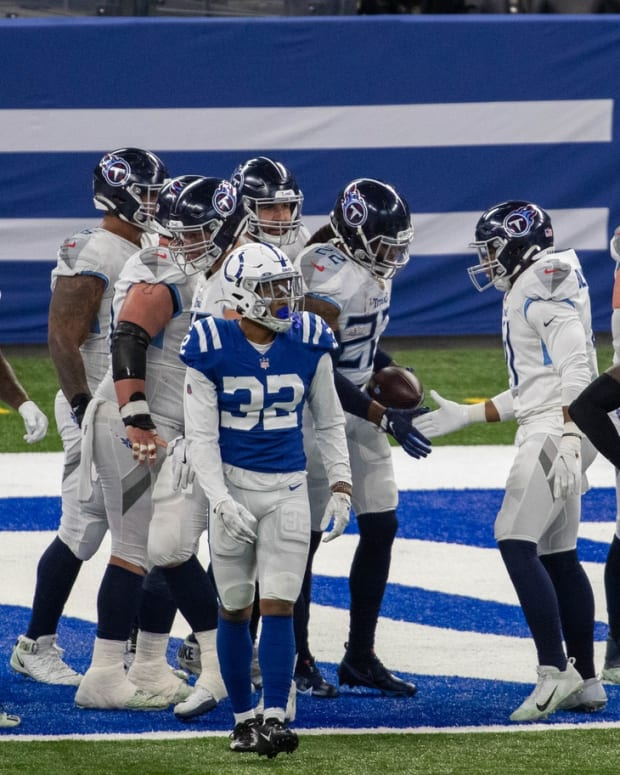 The Tennessee Titans celebrate Derrick Henry's third touchdown run of the first half against a dejected Indianapolis Colts defense on Sunday at Lucas Oil Stadium.