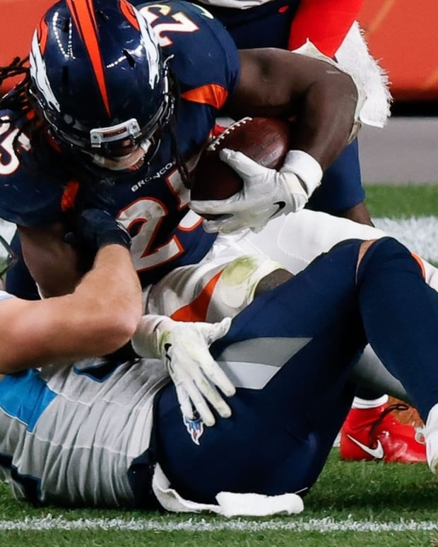 Denver Broncos running back Melvin Gordon III (25) scores a touchdown against Tennessee Titans inside linebacker Will Compton (53) and free safety Kevin Byard (31) in the fourth quarter at Empower Field at Mile High.
