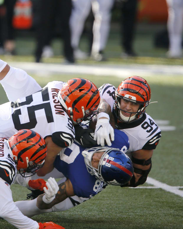 Nov 29, 2020; Cincinnati, Ohio, USA; New York Giants tight end Evan Engram (88) takes the hit from Cincinnati Bengals defensive end Sam Hubbard (94) and linebacker Logan Wilson (55) and linebacker Akeem Davis-Gaither (59) during the first quarter Paul Brown Stadium. Mandatory Credit: Joseph Maiorana-USA TODAY Sports