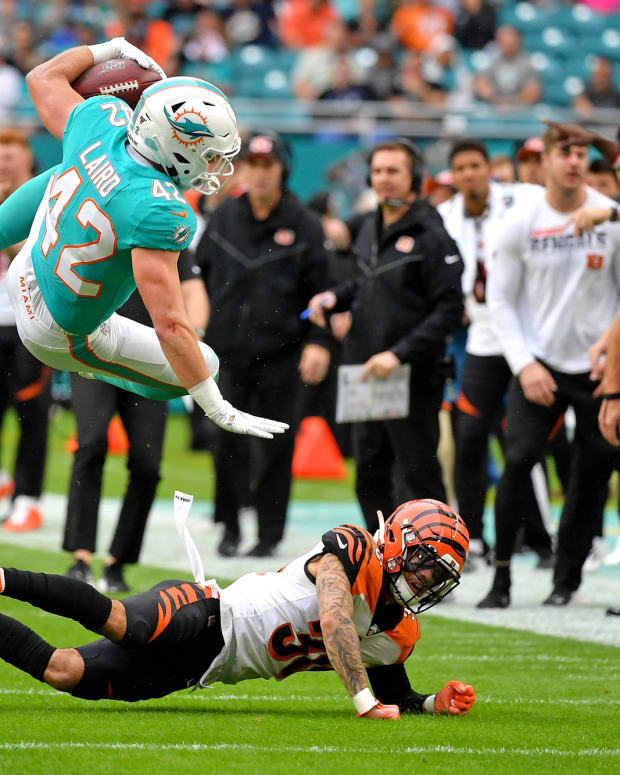 Dec 22, 2019; Miami Gardens, Florida, USA; Miami Dolphins running back Patrick Laird (42) leaps over Cincinnati Bengals free safety Jessie Bates (30) during the first half at Hard Rock Stadium. Mandatory Credit: Steve Mitchell-USA TODAY Sports
