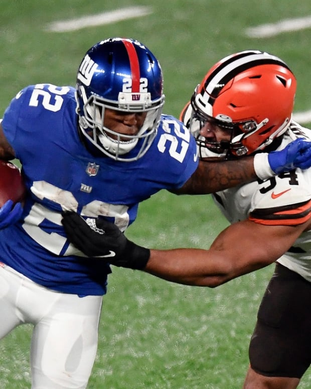 New York Giants running back Wayne Gallman (22) stiff-arms Cleveland Browns defensive end Olivier Vernon (54) in the second half. The Giants lose to the Browns, 20-6, at MetLife Stadium on Sunday, December 20, 2020, in East Rutherford.