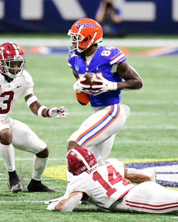 Dec 19, 2020; Atlanta, Georgia, USA; Florida Gators tight end Kyle Pitts (84) makes a catch against Alabama Crimson Tide defensive back Daniel Wright (3) and Alabama Crimson Tide defensive back Brian Branch (14) at Mercedes-Benz Stadium.