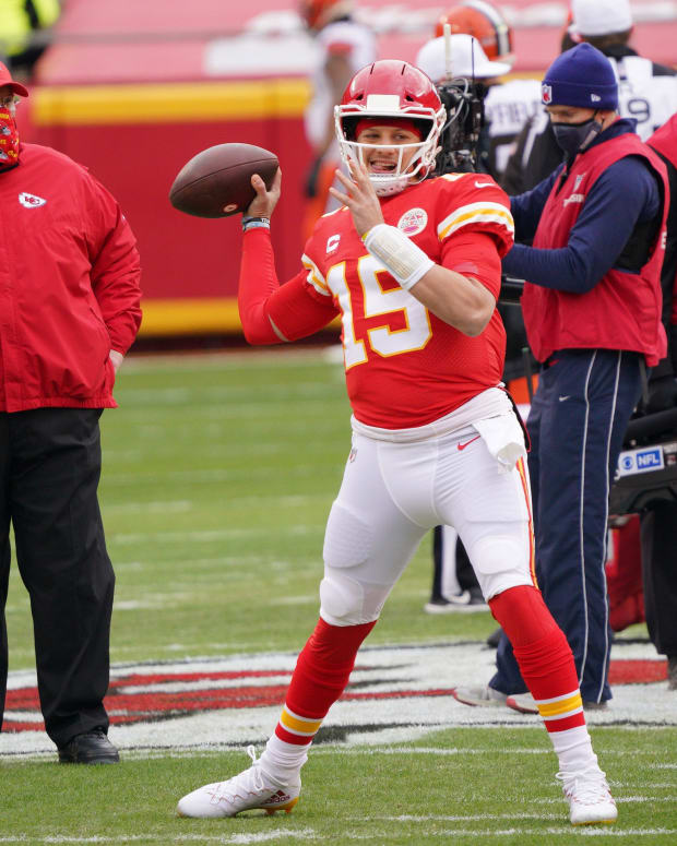 Jan 17, 2021; Kansas City, Missouri, USA; Kansas City Chiefs quarterback Patrick Mahomes (15) throws as head coach Andy Reid watches warmups before playing against the Cleveland Browns in the AFC Divisional Round playoff game at Arrowhead Stadium. Mandatory Credit: Denny Medley-USA TODAY Sports