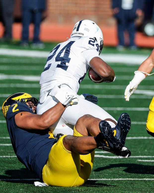 Michigan defensive lineman Carlo Kemp tackles Penn State running back Keyvone Lee during the first half of Michigan's 27-17 loss at Michigan Stadium on Saturday, Nov. 28, 2020.