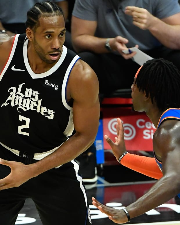 Jan 22, 2021; Los Angeles, California, USA; LA Clippers forward Kawhi Leonard (2) keeps the ball away from Oklahoma City Thunder forward Luguentz Dort (5) during the fourth qiuarter at Staples Center. Mandatory Credit: Robert Hanashiro-USA TODAY Sports
