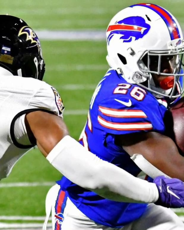 Bills running back Devin Singletary (26) runs the ball as Baltimore Ravens strong safety Chuck Clark (36) defends during the second half of an AFC Divisional Round playoff game at Bills Stadium