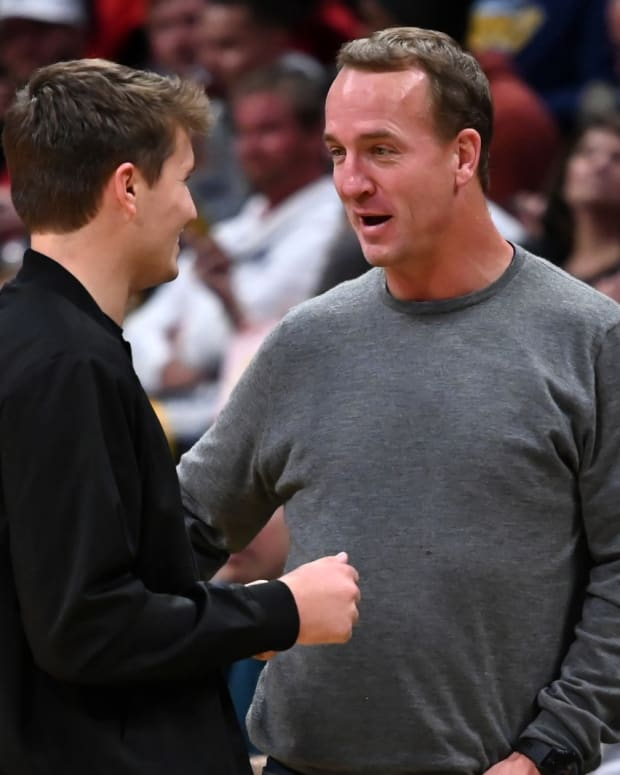 enver Broncos quarterback Drew Lock (left) talks with retired NFL quarterback Peyton Manning (right) during the game between the Toronto Raptors against the Denver Nuggets at the Pepsi Center.