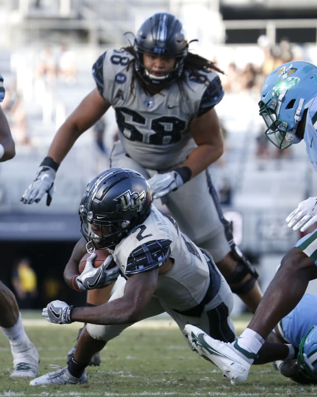 Oct 24, 2020; Orlando, Florida, USA; Tulane Green Wave linebacker Nick Anderson (40) tackles UCF Knights running back Otis Anderson (2) by the ankles as Green Wave safety Larry Brooks (31) and defensive end Patrick Johnson (7) and Knights offensive lineman Marcus Tatum (68) look on during the second half at the Bounce House.