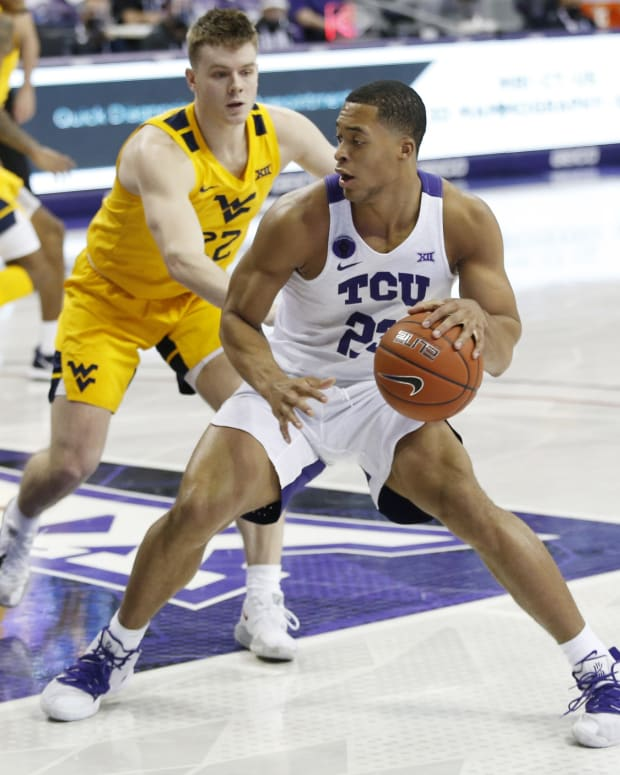 Feb 23, 2021; Fort Worth, Texas, USA; TCU Horned Frogs guard RJ Nembhard (22) dribbles against West Virginia Mountaineers guard Sean McNeil (22) during the first half at Ed and Rae Schollmaier Arena.