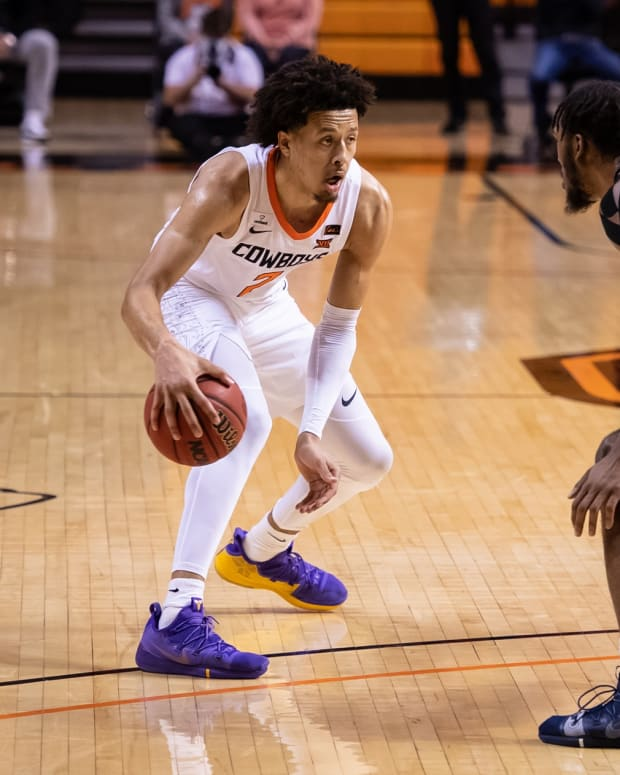 Jan 4, 2021; Stillwater, Oklahoma, USA; Oklahoma State Cowboys guard Cade Cunningham (2) dribbles against West Virginia Mountaineers forward Derek Culver (1) during the second half at Gallagher-Iba Arena.