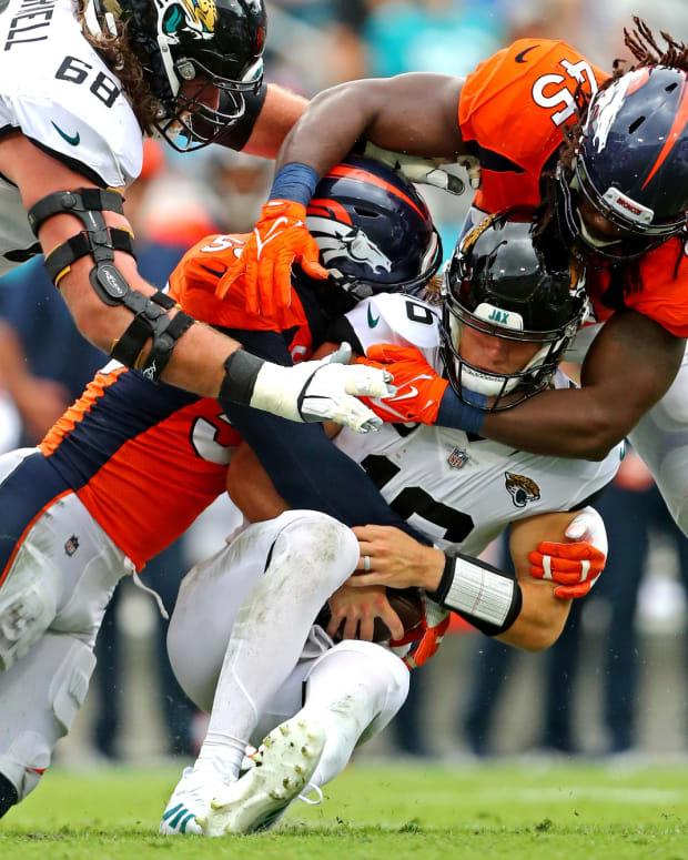 Jacksonville Jaguars quarterback Trevor Lawrence (16) is sacked by Denver Broncos outside linebacker Von Miller (58) and linebacker A.J. Johnson (45) during the second half at TIAA Bank Field.