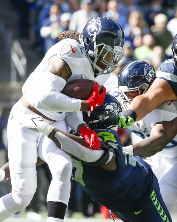 Seattle Seahawks defensive tackle Poona Ford (97) tackles Tennessee Titans running back Derrick Henry (22) during the first quarter at Lumen Field.