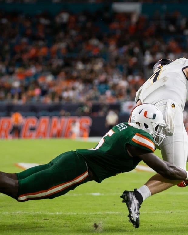 Sep 11, 2021; Miami Gardens, Florida, USA; Miami Hurricanes safety Amari Carter (5) tackles Appalachian State Mountaineers quarterback Chase Brice (7) during the fourth quarter at Hard Rock Stadium. Mandatory Credit: Richard Graulich-USA TODAY Sports