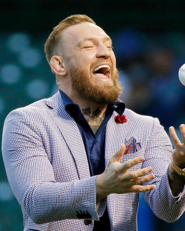 Sep 21, 2021; Chicago, Illinois, USA; MMA fighter Conor McGregor tosses the ball after throwing out a ceremonial first pitch before the game between the Chicago Cubs and the Minnesota Twins at Wrigley Field. Mandatory Credit: Jon Durr-USA TODAY Sports