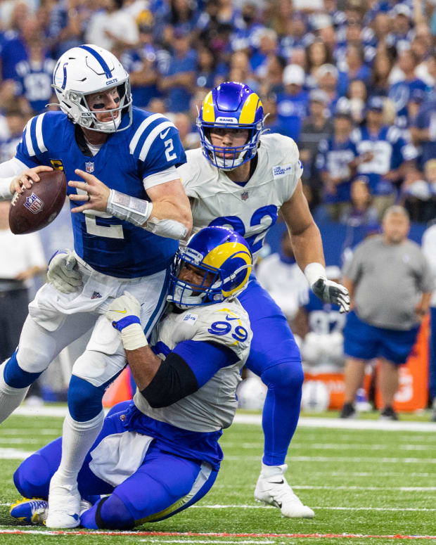 Sep 19, 2021; Indianapolis, Indiana, USA; Indianapolis Colts quarterback Carson Wentz (2) runs with the ball while Los Angeles Rams defensive end Aaron Donald (99) defends in the second half at Lucas Oil Stadium.