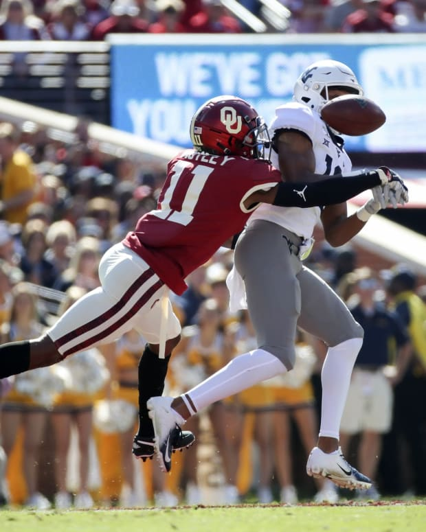 Oct 19, 2019; Norman, OK, USA; Oklahoma Sooners cornerback Parnell Motley (11) defends a pass intended for West Virginia Mountaineers wide receiver Ali Jennings (19) during the second quarter at Gaylord Family - Oklahoma Memorial Stadium.