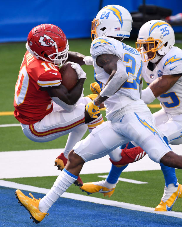 Sep 20, 2020; Inglewood, California, USA; Kansas City Chiefs wide receiver Tyreek Hill (10) falls into the end zone for a touchdown while defended by Los Angeles Chargers safety Nasir Adderley (24) and cornerback Chris Harris (25) during the fourth quarter at SoFi Stadium. Mandatory Credit: Robert Hanashiro-USA TODAY Sports