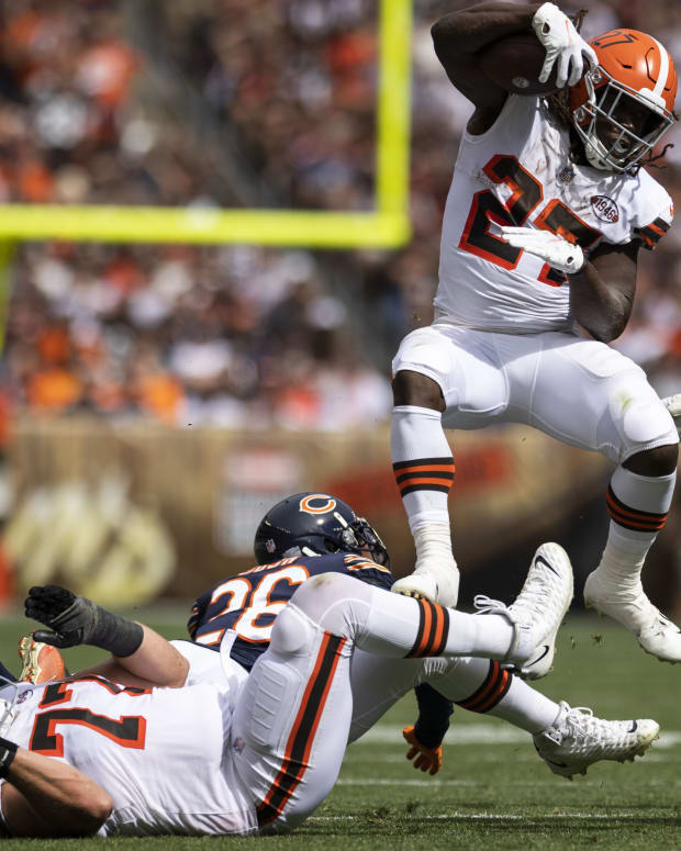 Sep 26, 2021; Cleveland, Ohio, USA; Cleveland Browns running back Kareem Hunt (27) leaps over offensive guard Wyatt Teller (77) and Chicago Bears defensive back Deon Bush (26) during the second quarter at FirstEnergy Stadium. Mandatory Credit: Scott Galvin-USA TODAY Sports
