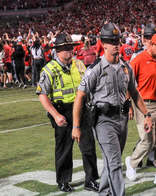 Clemson head coach Dabo Swinney walks by NC State celebrating their 27-21 win in two overtimes game at Carter-Finley Stadium in Raleigh, N.C., September 25, 2021.