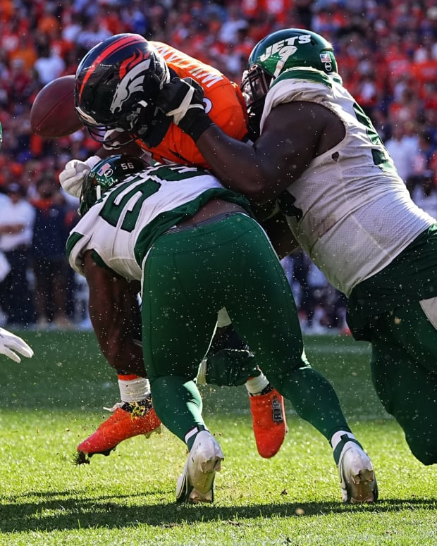 Denver Broncos running back Javonte Williams (33) fumbles the ball after a tackle by New York Jets outside linebacker Quincy Williams (56) and defensive tackle Foley Fatukasi (94) in the fourth quarter at Empower Field at Mile High.