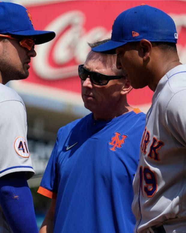 Aug 22, 2021; Los Angeles, California, USA; New York Mets manager Luis Rojas (19) and a team trainer talk to New York Mets third baseman J.D. Davis (28) after he took a hard grounder off his hand in the third inning against the Los Angeles Dodgers at Dodger Stadium.