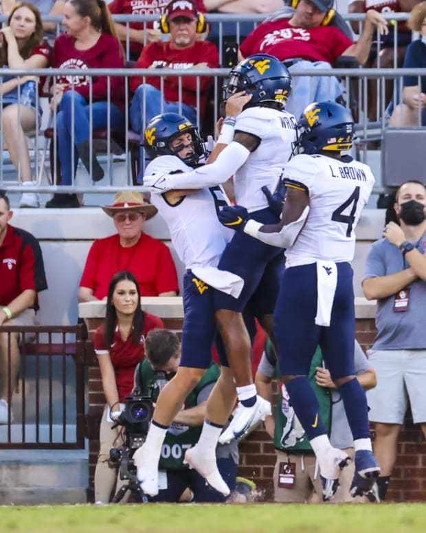 Sep 25, 2021; Norman, Oklahoma, USA; West Virginia Mountaineers quarterback Garrett Greene (6) celebrates with teammates after scoring a touchdown during the first quarter against the Oklahoma Sooners at Gaylord Family-Oklahoma Memorial Stadium.