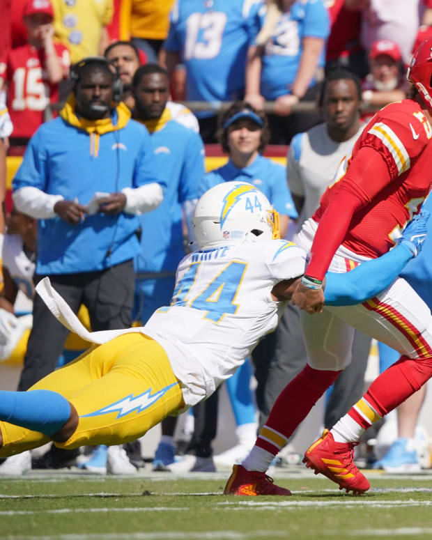 Kansas City Chiefs quarterback Patrick Mahomes (15) is tackled by Los Angeles Chargers outside linebacker Kyzir White (44) during the first half at GEHA Field at Arrowhead Stadium.