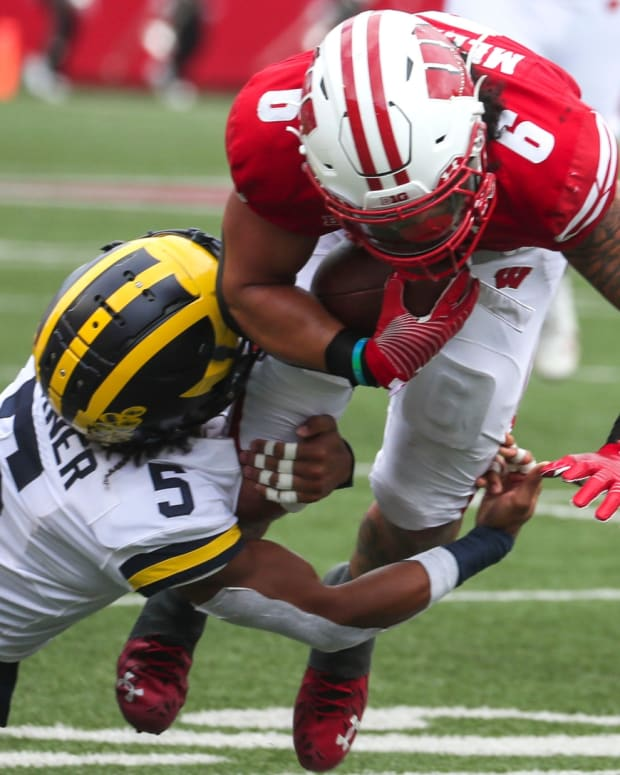 Wisconsin Badgers running back Chez Mellusi (6) runs the ball as Michigan Wolverines defensive back DJ Turner (5) tackles him during their game Saturday, Oct. 2, 2021, at Camp Randall Stadium in Madison, Wis. Ebony Cox / Milwaukee Journal Sentinel
