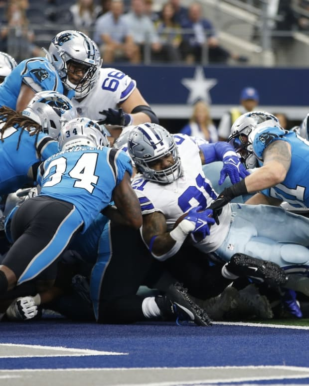 Oct 3, 2021; Arlington, Texas, USA; Dallas Cowboys running back Ezekiel Elliott (21) scores a touchdown against Carolina Panthers defensive back Sean Chandler (34) in the first quarter at AT&T Stadium. Mandatory Credit: Tim Heitman-USA TODAY Sports