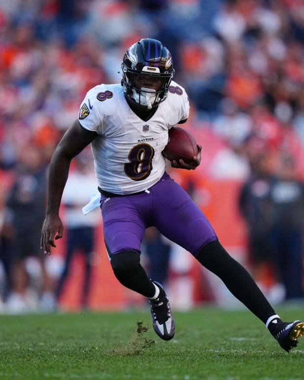 Oct 3, 2021; Denver, Colorado, USA; Baltimore Ravens quarterback Lamar Jackson (8) carries the ball in the third quarter against the Denver Broncos at Empower Field at Mile High. Mandatory Credit: Ron Chenoy-USA TODAY Sports